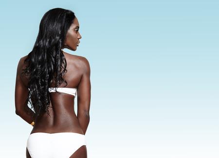 Frau von der Rückseite mit dem langen lockigen Haar trägt Bikini LANG_EVOIMAGES