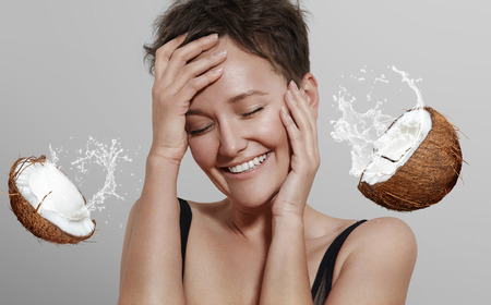 happy laughing girl on a grey background with a coconut and splashes of a cocomilk Stockfoto