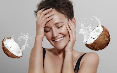 coco: Muchacha de risa feliz en un fondo gris con un coco y salpicaduras de un cocomilk