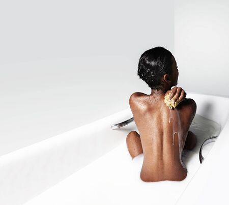 body milk: black woman in white bathroom with milk LANG_EVOIMAGES
