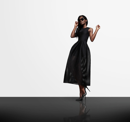 e shopping: woman wearing black dress on a white wall background and black cristal flor