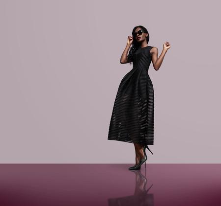 femme africaine: mannequin portant robe noire et lunettes de soleil LANG_EVOIMAGES