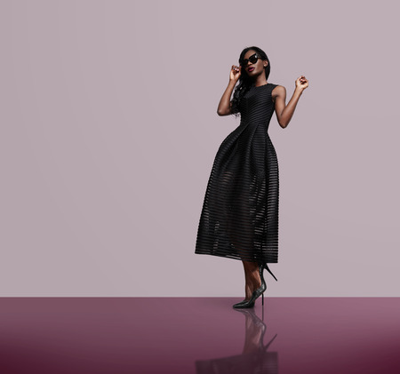 moda: modelka ma na sobie czarną sukienkę i okulary