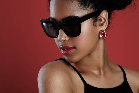 pietre preziose: woman wearing sunglasses and shiny earrings LANG_EVOIMAGES