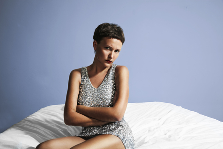 indifferent: displeased woman prepeared to party and sitting on a bed Stock Photo