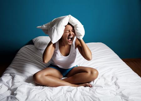 ベッドの上の女性別れてスクリーミン、枕で彼女の耳を閉じると