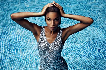 mojada: belleza de la mujer mojada en traje de coctail en la piscina de natación