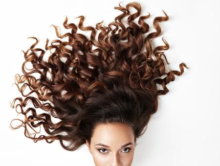 modelo: pelo rizado y parte de la cara de la mujer, mirando a la cámara
