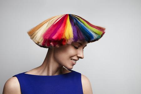여자는 그녀의 무지개 색 머리를 흔들
