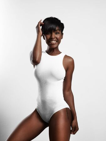 jamaican adult: perfect shaped woman wearing white body suit and smiling LANG_EVOIMAGES