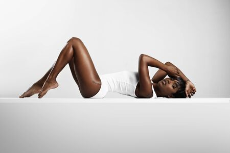 black women hair: beauty woman in body suit posing and showing perfect body
