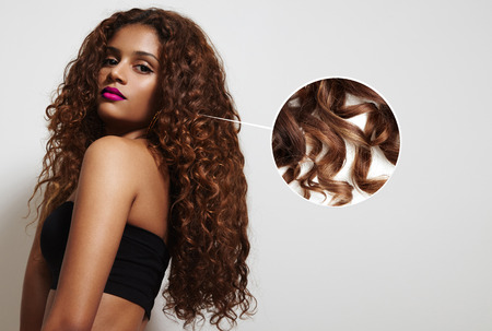 schoonheid Latijnse vrouw met krullend haar en loupe laat haar haren