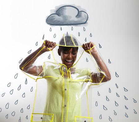 jovenes felices: Mujer en impermeable negro transparente con lluvia dibujado y la nube LANG_EVOIMAGES