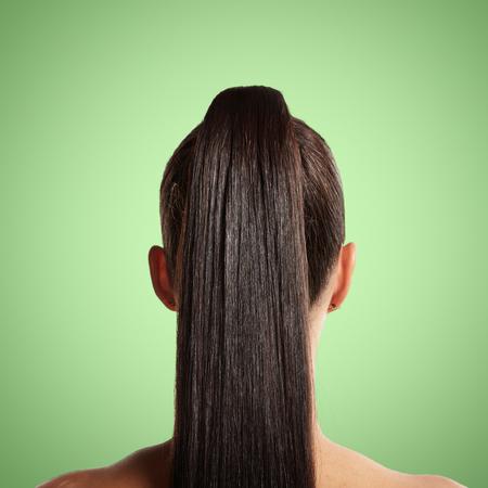 cola mujer: primer plano de cola de caballo. fondo verde
