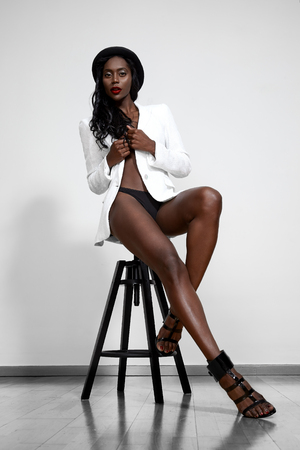 topless black woman wearing white jacket and hat photo