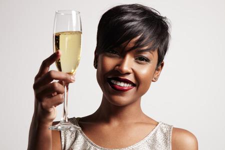 mujeres negras: mujer con una copa de champán. Celebrando y sonriente