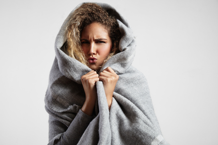 winter day: woman feeling freeze and wrap up in a blanket