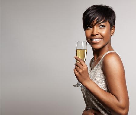 schwarz: Frau mit einem Glas Champagner. Feiert und lächelnd LANG_EVOIMAGES