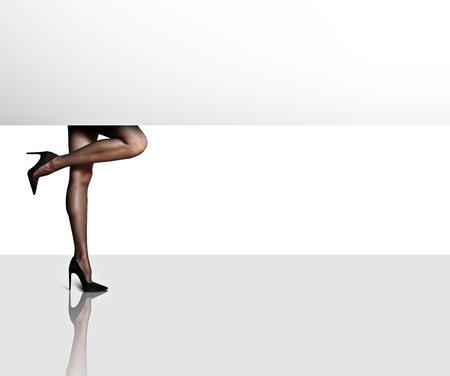 femenine: womans legs behind the white card