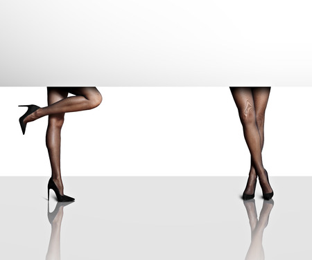 heals: two womans legs in a white space with reflection LANG_EVOIMAGES