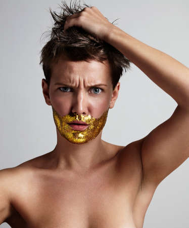 femenine: nude woman with a golden gliter in a shape of beard