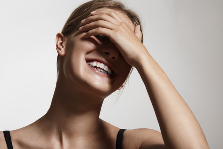 impacted: woman in braces is laughing and close her eyes with a hand LANG_EVOIMAGES