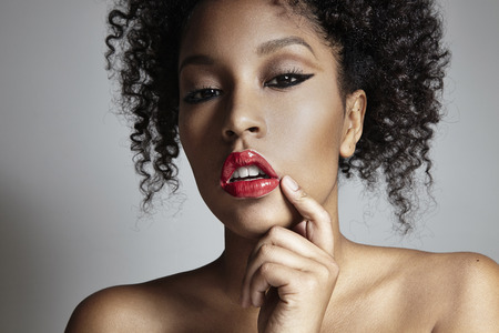 mulatto woman: mulatto woman corrects a lipstick with finger LANG_EVOIMAGES