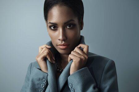 picks: woman picks up collar of coat LANG_EVOIMAGES