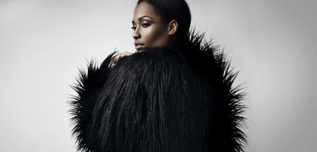 african american nude: black woman wears black faix fur jacket LANG_EVOIMAGES