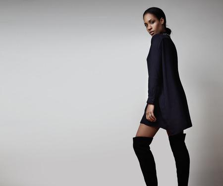 mannequin africain: beauté modèle noir poing dans de hautes bottes