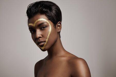 mooie vrouwen: zwarte vrouw wit een hartvorm op haar gezicht kijken naar de camera LANG_EVOIMAGES