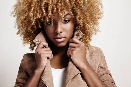 cabello negro: mujer de negro viste chaqueta de color beige, pelo rizado