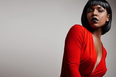 빨간 드레스를 입고 똑바로 짧은 머리를 가진 흑인 여성 스톡 콘텐츠