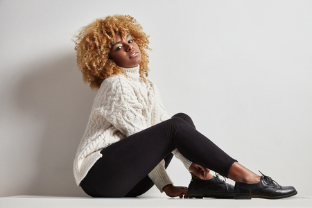 blondy: blondy black woman with a curly hair sitting in a knitted jersey
