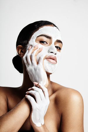 white mask: Woman during facial treatment. white cream mask on her face and hands LANG_EVOIMAGES