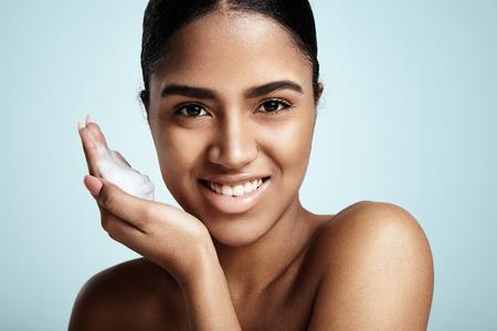 Mujer latina negro con una espuma facial en una mano. listo para aplicar Foto de archivo