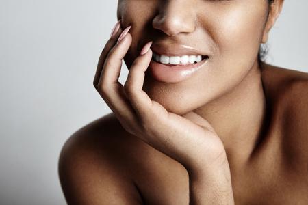gros plan photo des lèvres de la femme, en souriant et en touchant sa joue