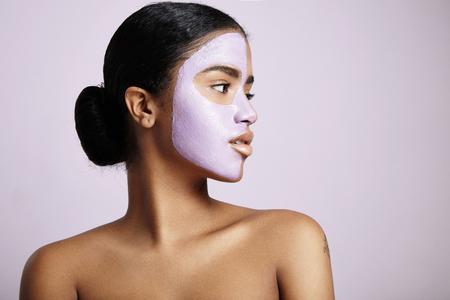 顔のマスクを持つ女性に見える紫色の背景に脇