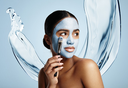 woman put facial mask, water splash on a background Banque d'images