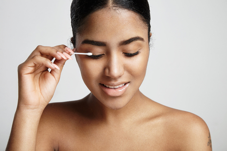 african beauty: woman with a cotton swab stick clean her eyelid LANG_EVOIMAGES