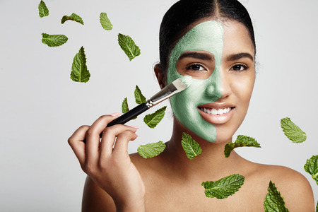 natural therapy: woman with a fresh green mask with avocado and mint leavs in air