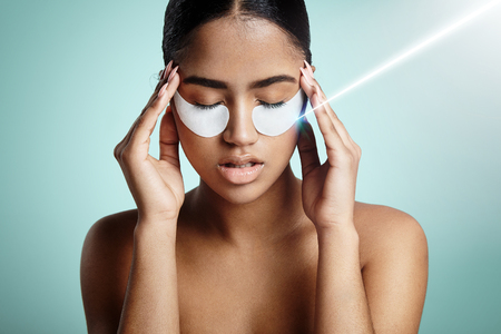 face mask: skin stress concept with a rey of light on eye patch LANG_EVOIMAGES