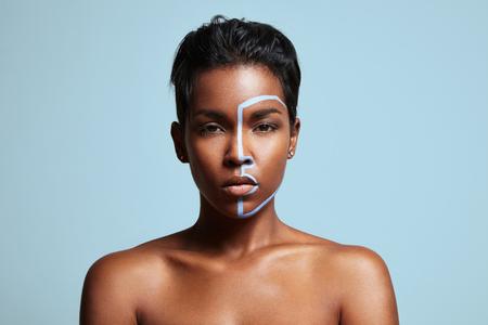 femme noire nue: femme avec ligne bleue sur un visage