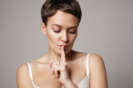 shush: woman with a finger close to mouth in a fine gesture