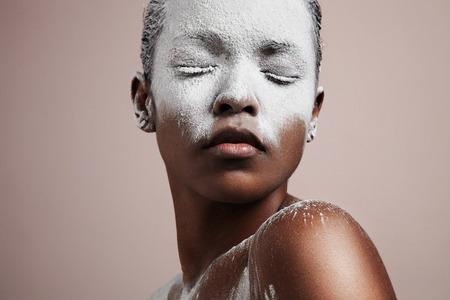 白い粉と黒の女性は、顔を覆った。美容治療。低温によって損傷皮膚