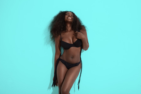 beauty black woman in a black bikini on a blue background