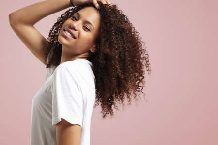 black hair: happy smiling woman touching her curly hair LANG_EVOIMAGES