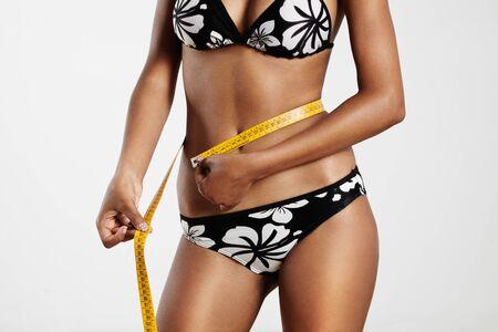 mesure: woman with a tape measure on a waistline