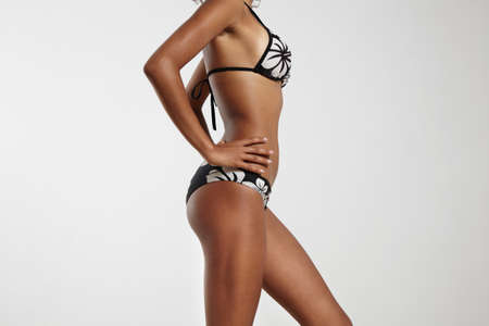mesure: woman with ideal body in bikini on a grey background