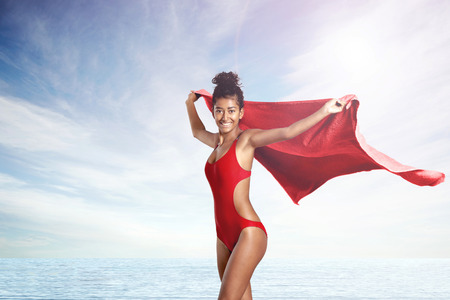 mesure: woman in red swimsuit of life guard with red towell on a beach